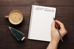 Taza de escritura de la mano del café y del varón en las metas del cuaderno para 2017 desde arriba Planeamiento y motivación para Fotos de archivo libres de regalías