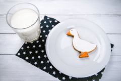 Taza de galletas del duckshape de la leche y del jengibre en una tabla de madera blanca y un naplin azul marino con las estrellas imagen de archivo libre de regalías