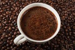 Taza de granos de café en la tabla Imagenes de archivo