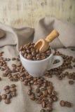 Taza de granos de café en tela en fondo gris Foto de archivo