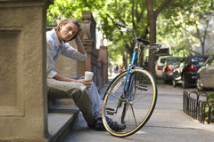Taza de Holding Disposable Coffee del hombre de negocios mientras que se sienta en pasos Fotos de archivo libres de regalías
