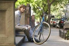 Taza de Holding Disposable Coffee del hombre de negocios mientras que se sienta en pasos Fotos de archivo
