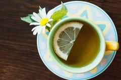 Taza de infusión de hierbas con la manzanilla y el limón en el fondo de madera Imagenes de archivo
