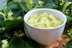 Taza de infusión de hierbas con las flores del tilo en una taza blanca en un fondo de madera imagenes de archivo