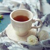 Taza de juego de té con una toalla y las rosas de té hermosa en un de madera Foto de archivo