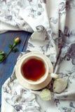 Taza de juego de té con una toalla y las rosas de té hermosa en un de madera Foto de archivo libre de regalías