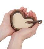 Taza de la arcilla bajo la forma de corazón con una cuchara Imágenes de archivo libres de regalías