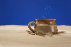 Taza de la arcilla con té o café en la arena de la playa Imágenes de archivo libres de regalías