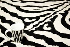 Taza de la cebra en la alfombra de la cebra Fotos de archivo libres de regalías