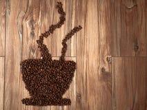 Taza de la composición de café hecha por los granos de café Imagen de archivo