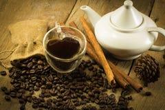 Taza de la forma del corazón, granos de las teteras y de café en de madera Imagenes de archivo