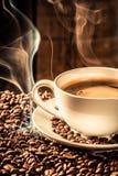 Taza de la fragancia de café con los granos asados imagenes de archivo
