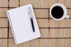 Taza de la libreta, de la pluma y de café. Imágenes de archivo libres de regalías