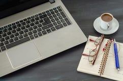 Taza de la libreta, del ordenador portátil y de café en la tabla de madera imágenes de archivo libres de regalías