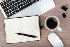 Taza de la libreta, del ordenador portátil y de café en la tabla de madera fotografía de archivo