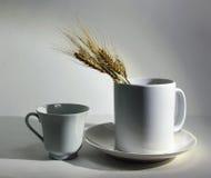 taza de la loza y oídos blancos del trigo en un fondo blanco Foto de archivo libre de regalías