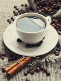 Taza de la mañana de café con los palillos de canela Imagenes de archivo