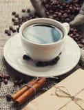 Taza de la mañana de café con los palillos de canela Imágenes de archivo libres de regalías