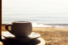 Taza de la mañana de café, por el mar Foto de archivo libre de regalías