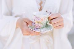 Taza de la mañana de té en manos femeninas fotografía de archivo libre de regalías