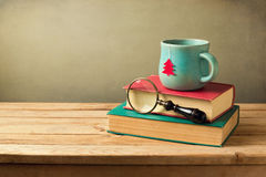 Taza de la Navidad de té y libros en la tabla de madera con el espacio de la copia Fotografía de archivo