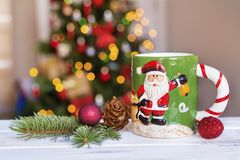 Taza de la Navidad en fondo ligero borroso Imagen de archivo