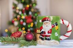 Taza de la Navidad en fondo ligero borroso Imágenes de archivo libres de regalías