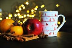 Taza de la Navidad de té y de frutas delante de un fondo luminoso Foto de archivo libre de regalías