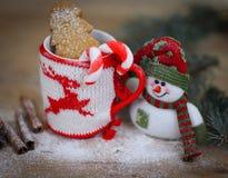 Taza de la Navidad y un muñeco de nieve del juguete en fondo de madera Imagen de archivo libre de regalías