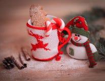 Taza de la Navidad y un muñeco de nieve del juguete en fondo de madera Fotografía de archivo libre de regalías