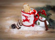 Taza de la Navidad y un muñeco de nieve del juguete en fondo de madera Foto de archivo