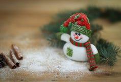 Taza de la Navidad y un muñeco de nieve del juguete en fondo de madera Imagenes de archivo