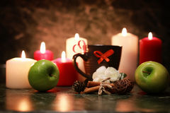 Taza de la noche de té con la vela y la manzana Foto de archivo libre de regalías