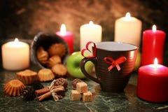 Taza de la noche de té con la vela y la manzana Fotografía de archivo libre de regalías