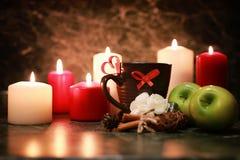 Taza de la noche de té con la vela y la manzana Foto de archivo