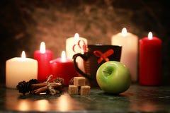 Taza de la noche de té con la vela y la manzana Fotos de archivo