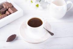 Taza de la porcelana de café sólo y de caramelos de chocolate en un fondo blanco fotos de archivo libres de regalías