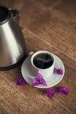 Taza de la porcelana con té negro y la caldera Fotografía de archivo