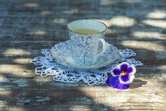 Taza de la porcelana de té en una tabla de madera en el jardín Partido del verano Fotografía de archivo libre de regalías