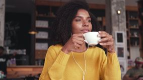 Taza de la tenencia de la mujer joven de música que escucha del café en los auriculares almacen de video