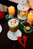 Taza de latte con la melcocha y de decoración de la Navidad en la tabla Imagen de archivo