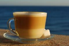 Taza de latte o de capuchino por el mar foto de archivo