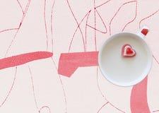 Taza de leche con el corazón en un fondo geométrico Fotos de archivo libres de regalías