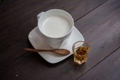 Taza de leche con la miel en la tabla de madera Fotografía de archivo