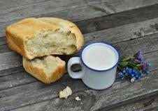 Taza de leche con pan y flores en la tabla vieja Fotografía de archivo libre de regalías