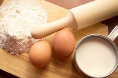 Taza de leche, de dos huevos y de harina Fotografía de archivo libre de regalías