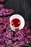 Taza de lila del té y del ramo fotografía de archivo