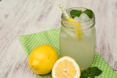 Taza de limonada y de limones en el fondo de madera blanco Imágenes de archivo libres de regalías
