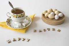 Taza de los huevos del té, blancos y amarillos de Pascua, letras de madera, contra la tabla blanca imagen de archivo