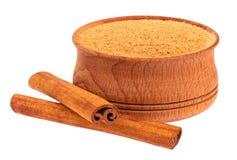 Taza de madera y dos palillos de canela Foto de archivo